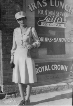 Ila Armsbury standing in front of her family's restaurant, Ira's Lunch, in Lincoln, Kansas, prior to December 7, 1941.